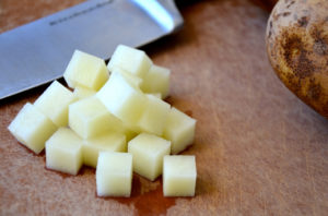 white potato in a small dice cut against a cuttingboard